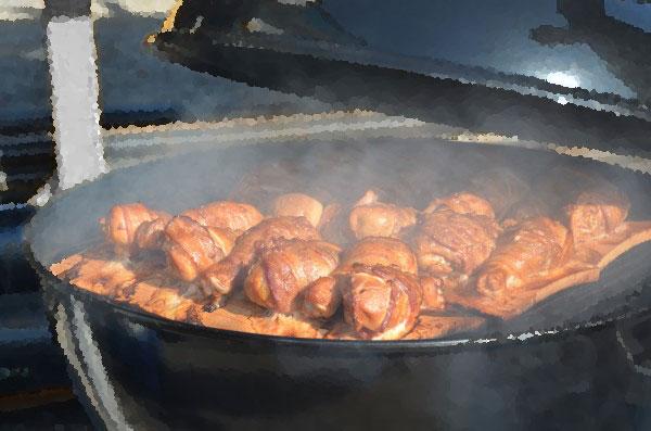 Pilon de poulet enrobé de bacon fumé sur la planche d'érable